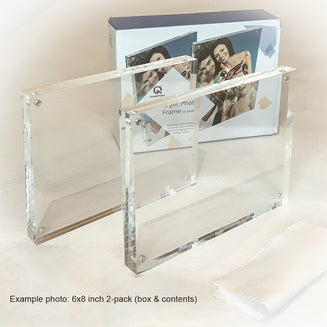A photo showing a box with Kluger Punkt photo frames and two frames next to it. The box has pictures of a smiling family on vacatons printed on it.