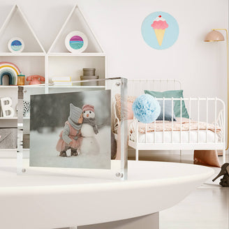 Kluger Punkt photo frame showing a little girl hugging a snow man. The photo frame stands on a table in a kids room.