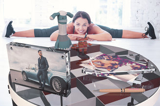 A beautiful girl doing her workout and looking at a table with two Kluger Punkt photo frames. One photo shows a handsome man next to a nice car and another the same man without a shirt.