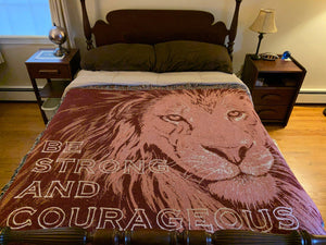 Lion Face Maroon Cotton woven blanket Be Strong and Courageous from original artwork of JungleCatArt.com artist Mary Anne Pellegrini shown on a full sized bed