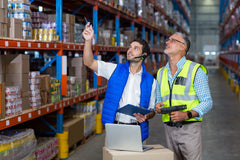 Two Men Working in a Warehouse Wearing Safety Vest