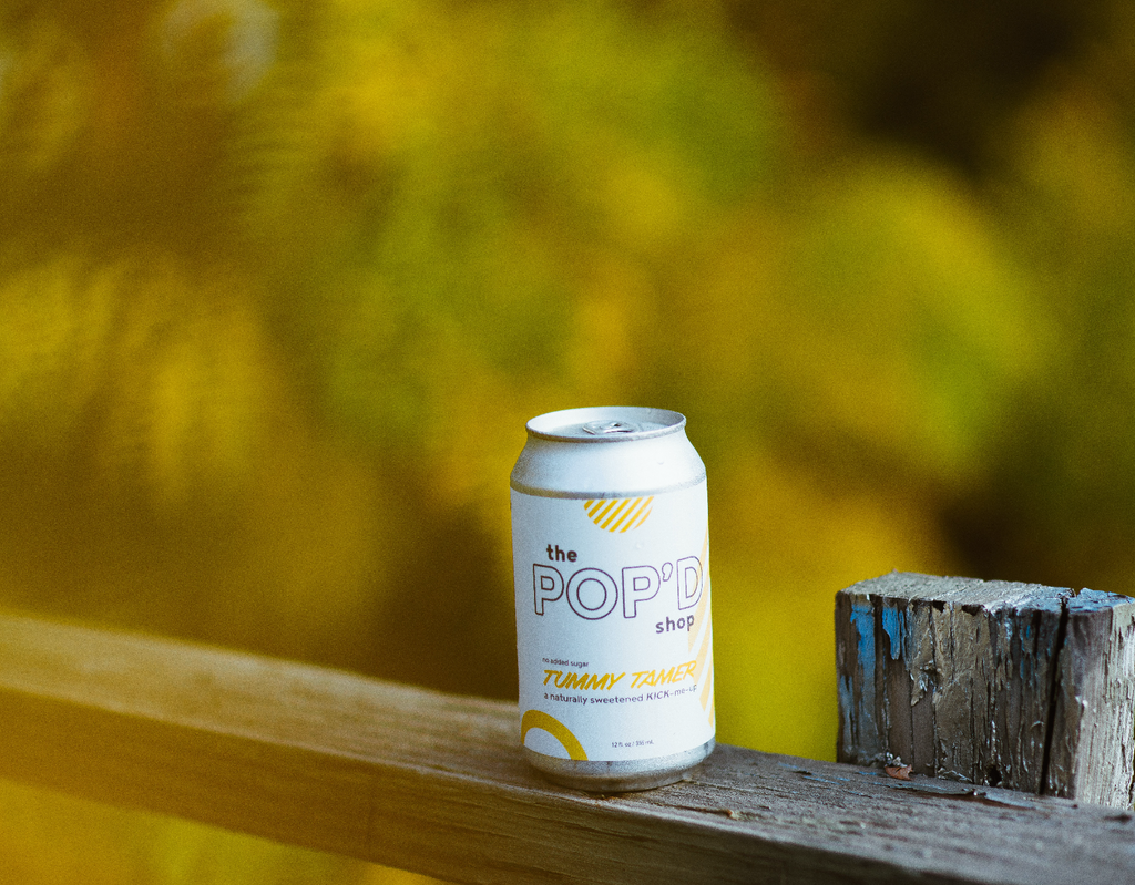 can of ginger, lemon, cayenne soda, outside, in front of green trees
