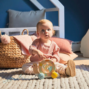 Janod Pure Pull-Along Snail | Wooden Toddler Activity Toy | Lifestyle – Baby Holding with Pure Pull-Along Snail | BeoVERDE.ie