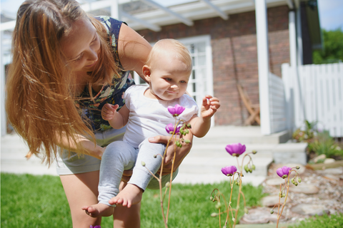 A mother and child smelling flowers