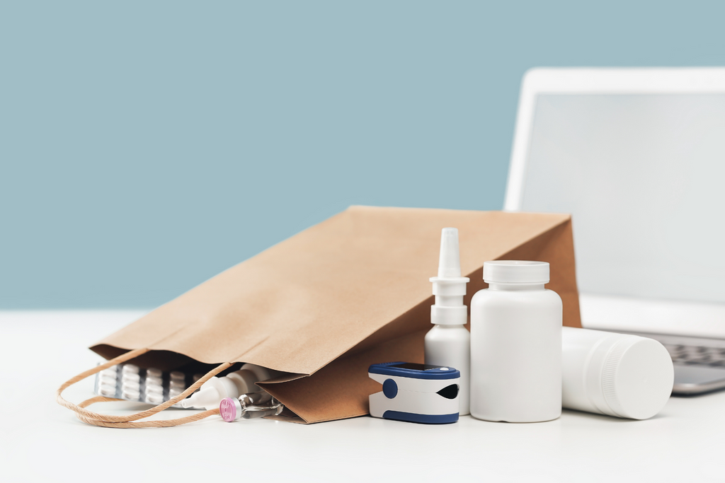 a delivery bag full of prescription medication in front of a laptop