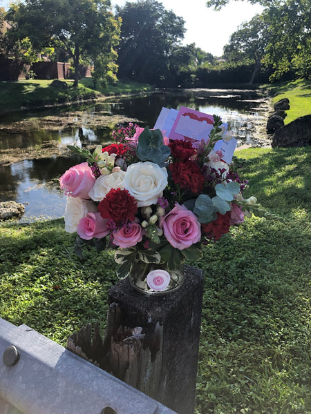 Pink Roses, White roses, Red Carnations, White Brunnia, Wax Flowe and varigated Pittosburum