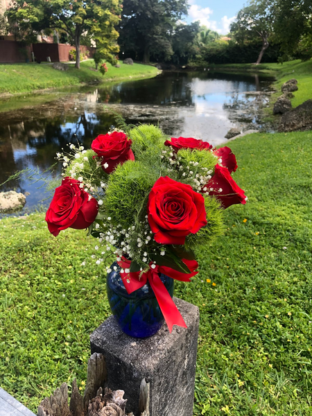 Red Roses , Dianthus and Gyp in a blue vase with a red Ribbon.
