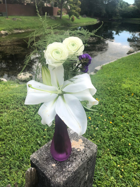 A white oriental lily accent with white ranunculus and greenery