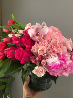 "A degradation of Hot Pink ideal for any type or event. Includes: Hot pink Tullips, Pink Hydrangea, Light Pink Spray Roses, Light Pink Cymb orchid, filling with Monsterra and greenery in a 6"" clear round vase."