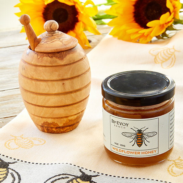 jar of honey, towel and olive wood honey pot with dipper