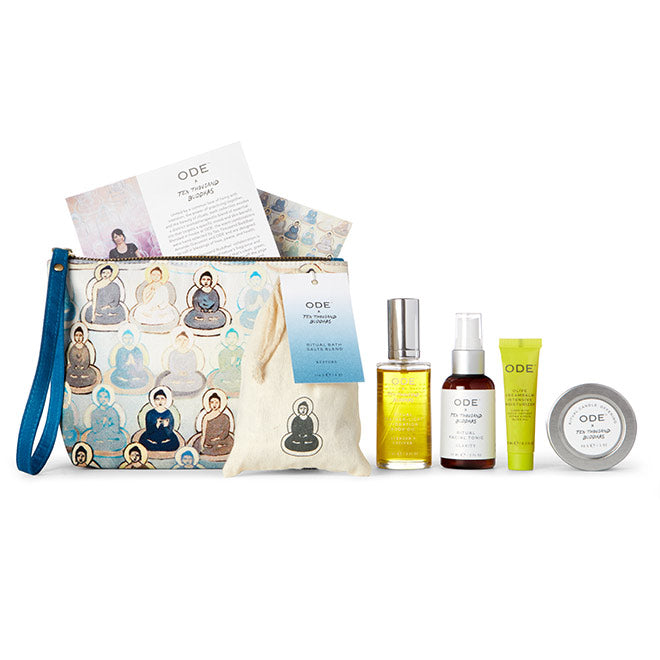candle, bath salts, body oil, tonic and moisturizer with blue cosmetic bag