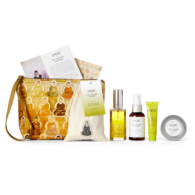 candle, bath salts, body oil, tonic and moisturizer with yellow cosmetic bag