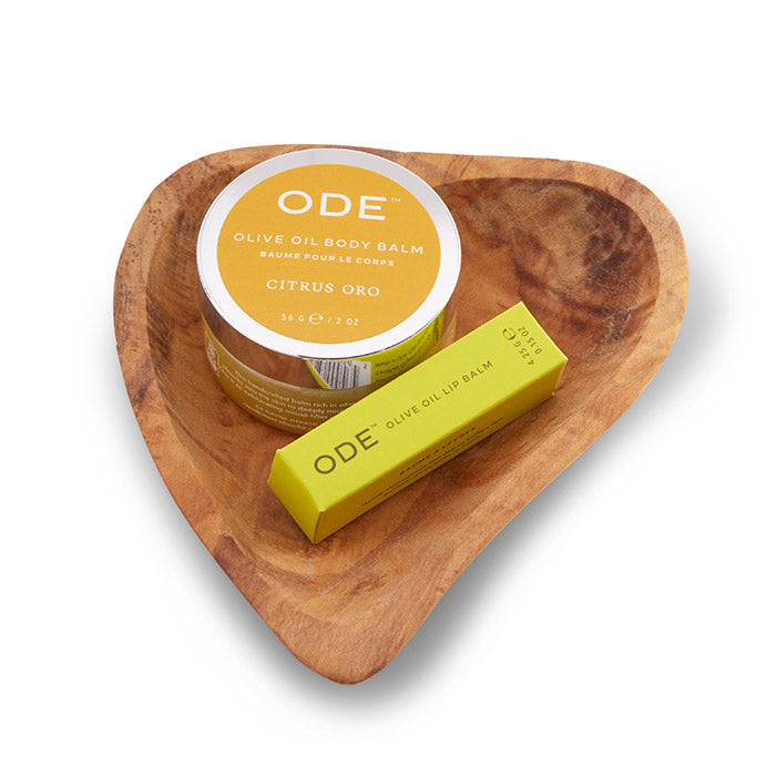 citrus oro body balm and lip balm on a teak heart shaped dish