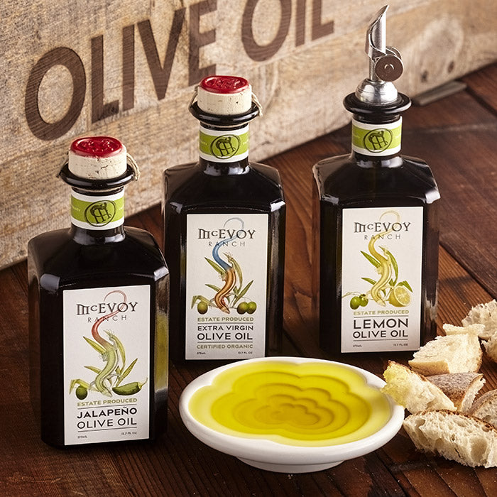 bottles of traditional blend extra virgin, lemon and jalapeño olive oil, oil pourer and dipping dish