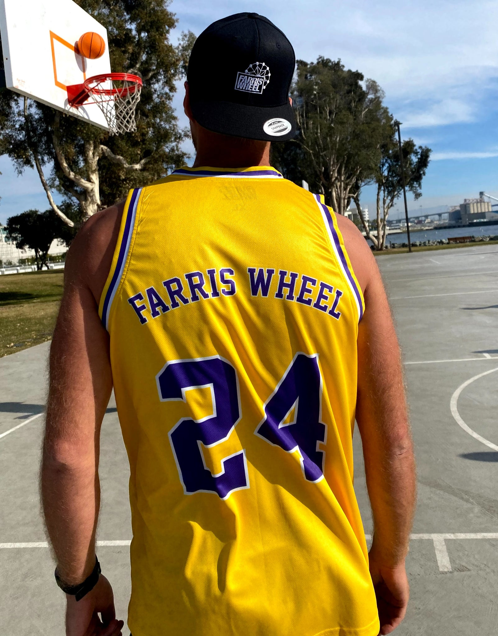 Man wears yellow Lakers Farris Wheel Jersey basketball t-shirt and black  snapback hat