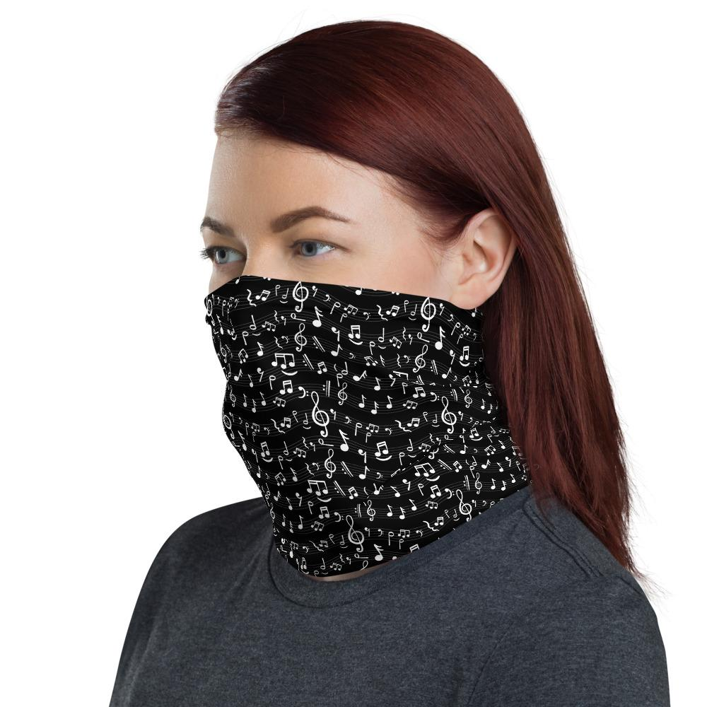 Woman wears black face cover with music notes pattern side view