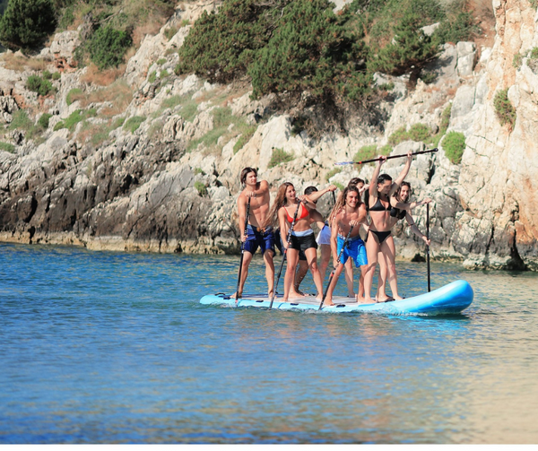 A large group of friends enjoys their time on the Aqua Marina Mega paddleboard.