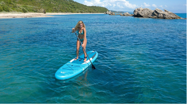 A woman rides on her blue blowup paddle board with gorgeous clear water beneath her.