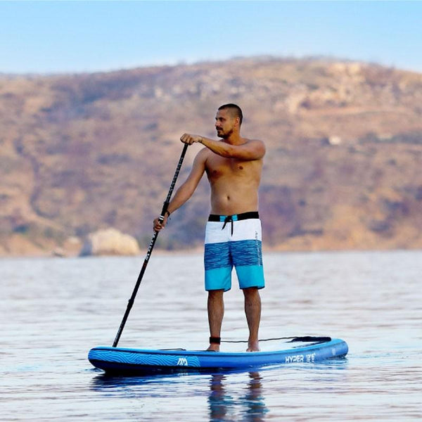 A man in blue swim-shorts gliding on the water aboard his Aqua Marina Hyper paddleboard.
