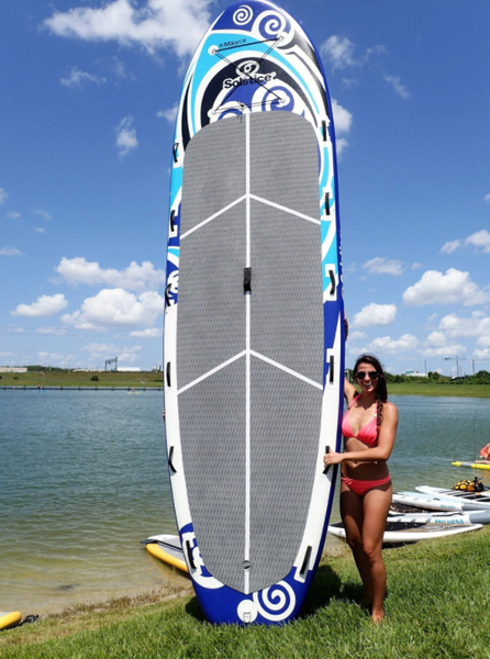 An image of a woman standing next to her gigantic inflatable paddeboard.