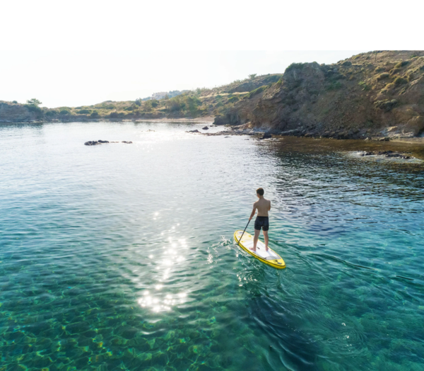 A preteen boy enjoys gliding across the water on his Aqua Marina Vibrant SUP.