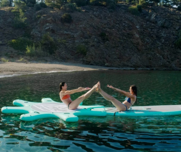 Two friends enjoy practicing yoga on their Aqua Marina yoga dock.