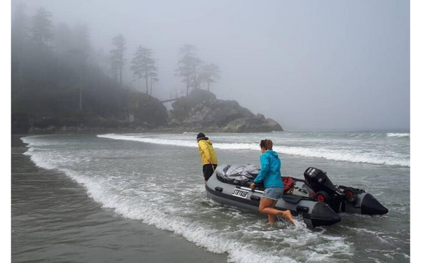 Two people drag their inflatable boat up to shore.