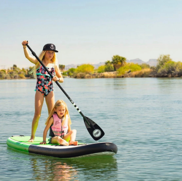 Two little sisters with blonde hair paddle board together.
