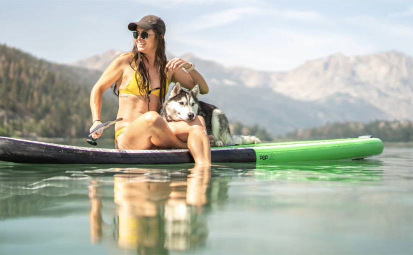 A woman in a yellow swimsuit relaxes on her black and green blowup paddleboard.