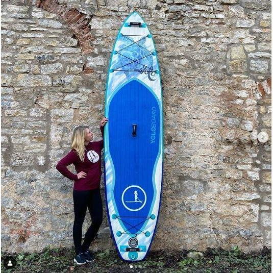 A woman gazes at the beautiful design of her Yolo Honu Blowup Paddle Board