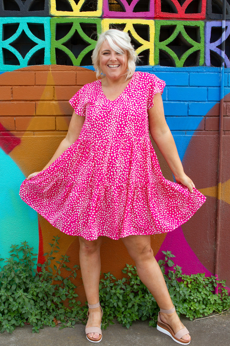 The Maeve Dress is a baby doll show stopper, our best selling style is here in a FUN print.   3 tiered hem skirt  Fluttered sleeves  Great length Generous sizing  V-neckline Slightly longer at the back Colour:  Pink with white dots Sizing:  Tara wears a size M & is 168CM Fabric:  100% Rayon Measurements: Size M  Bust: 53cm Arm Seam: 26cm Length: 90cm