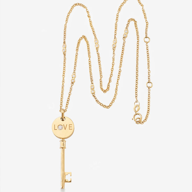 Kate & Mimi Mini Love Key with single round diamond on one side and round diamonds set pavé style on the other side styled view