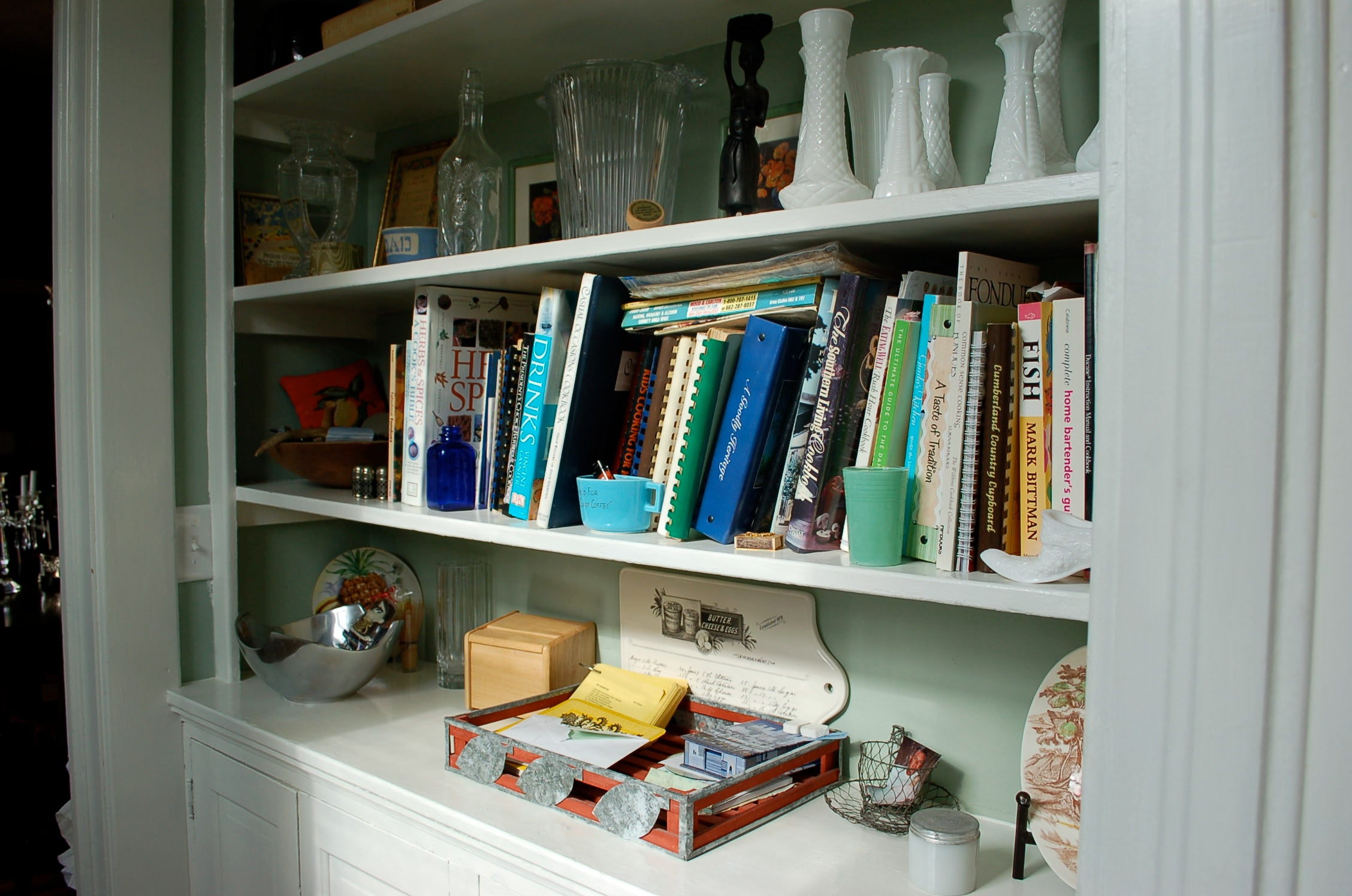 unorganized kitchen, book shelves, books, trinkets