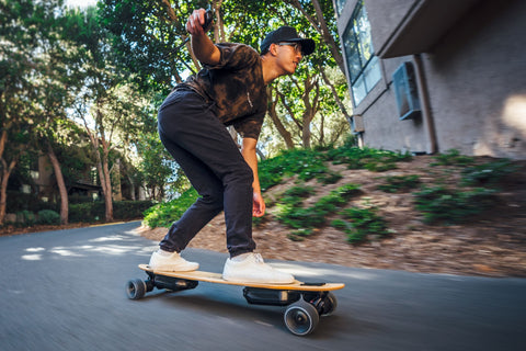 Man riding Omen Swarm longboard with Revel electric skateboard conversion kit installed