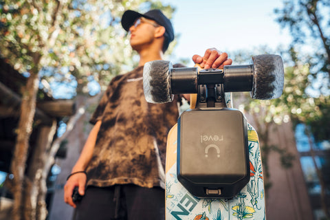 Man holding Omen Swarm longboard with Revel electric skateboard conversion kit and Cloudwheels installed
