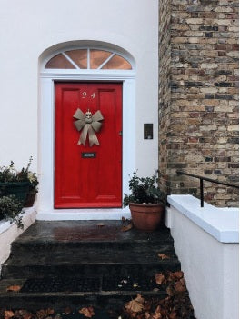A red front door with black hardware in the United Kingdom