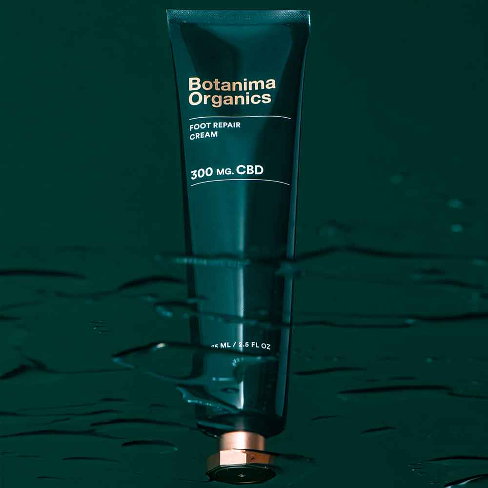 Foot-Repair-CBD-Cream-Tube-on-Green-Background-With-Water-Effect-Botanima-Organics-Premium-Skincare