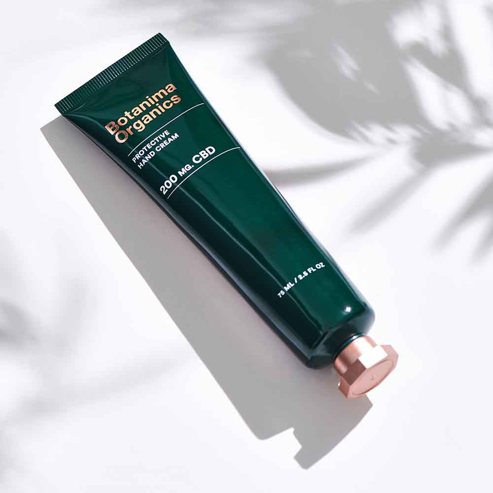 Protective-CBD-Hand-Cream-on-White-Background-With-Leaves-Shadow