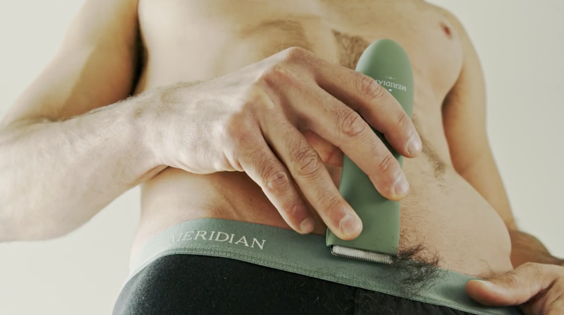 Man holding the the meridian ONYX color of the trimmer shaving the hair on his balls
