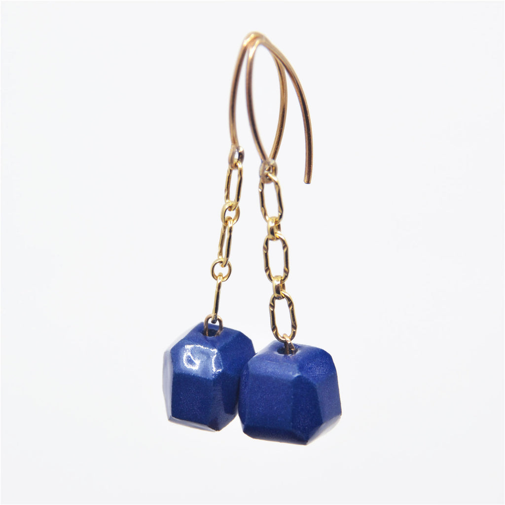 "One-of-a-kind gem cut blue porcelain bead earrings on 14 karat gold-filled chain dangle. Overall length 1 1/4"", faceted blue porcelain bead 3/8"" x 3/8"" x 3/8"".   14 karat gold-filled ear wire."