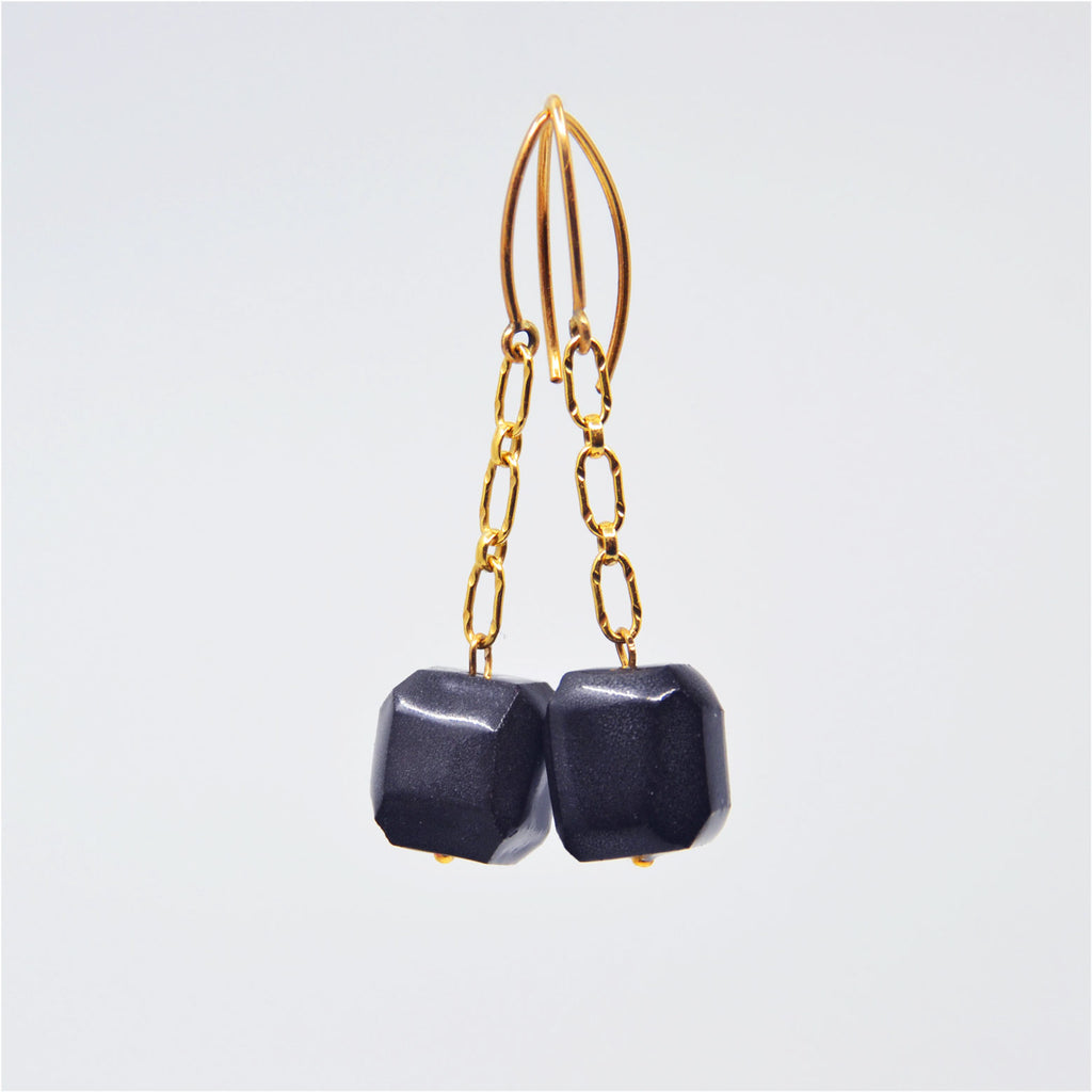 "One-of-a-kind gem cut black porcelain bead earrings on 14 karat gold-filled chain dangle. Overall length 1 3/8"". 14 karat gold-filled ear wire."
