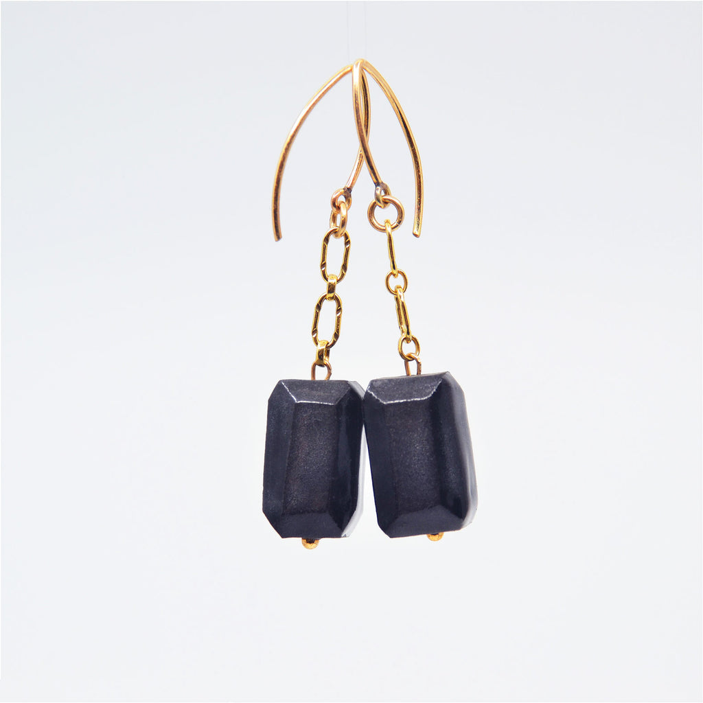 "One-of-a-kind gem cut black porcelain bead earrings on 14 karat gold-filled chain dangle. Overall length 1 1/4"". 14 karat gold-filled ear wire."