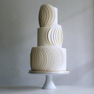 Modern sophisticated cake design with circular fondant panels in pleated formation
