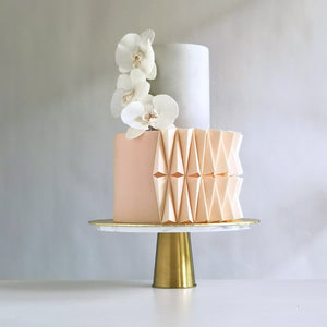 Gorgeous designer cake with pleated fondant detail that resembles Japanese-inspired origami