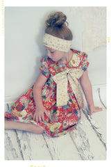 Red and Yellow floral girls dress with big oversized bow and peter pan collar and puff sleeves by Fleur + Dot