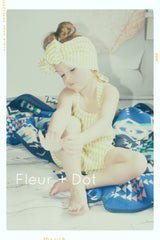 Handmade kids fashion. Oversized bow romper in lemon lime striped cotton.