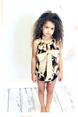 Girls romper bathing suit in cow print and mini vintage floral bow. Handmade by Fleur + Dot.