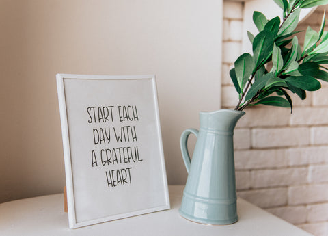 Positive quote in white frame next to a water jug of twigs.
