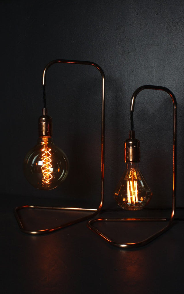 SMALL TRIANGULAR BASED COPPER LAMP with spiral incandescent bulb.