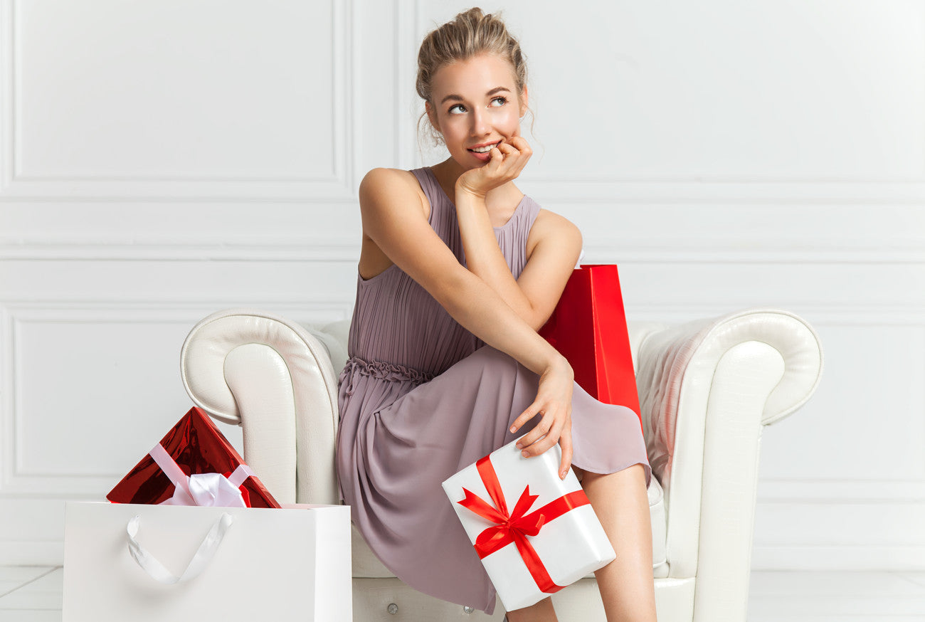 Woman sitting on a chair and holding a present in her hand